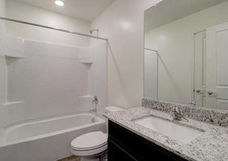 The Cottonwood floor plan bathroom with granite countertops and light on the ceiling over the bathtub/shower combo.