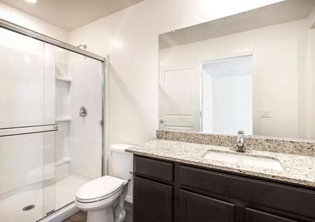 The Alamo floor plan master bath room shown with glass shower and granite sink countertops.