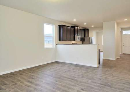 Columbia great room with wood flooring, white trimmed walls, and kitchen counter