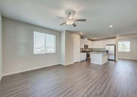 The spacious living, dining and kitchen area of the Loomis floor plan with wood-like flooring throughout the areas.