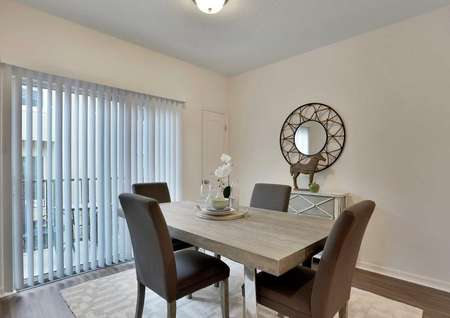 The Pine Key floor plans dining area has brown chairs, a light brown table and a rug under them.