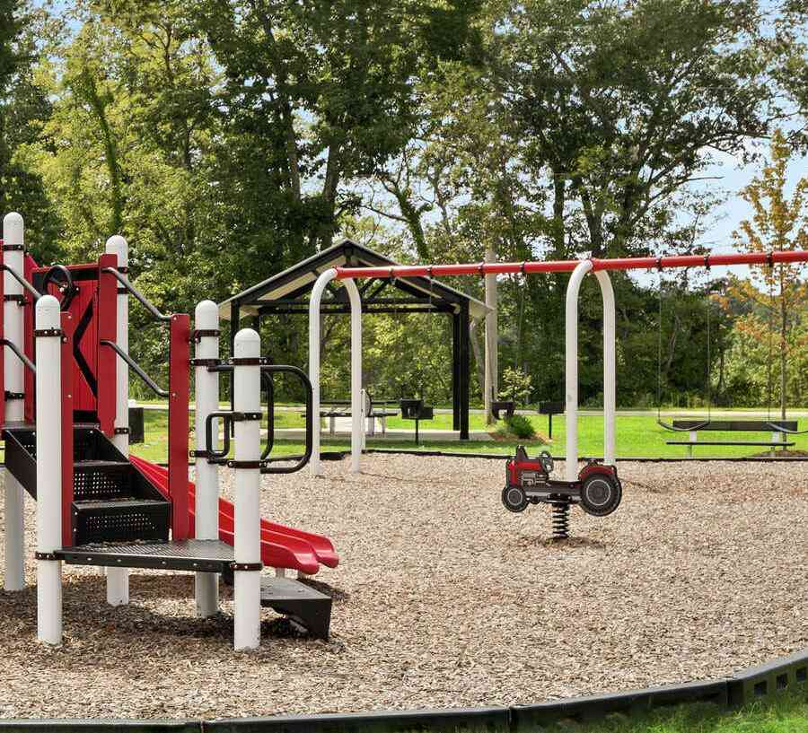 Honey Farms Playground overview of the climbing and slide sets as well as the swing set, large trees and landscaped grounds.jpg
