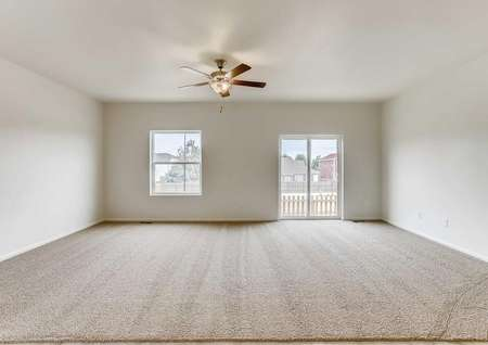 Princeton family room with backyard window and door, ceiling fan/light fixture, and light color carpet