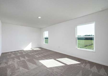 Sizable master bedroom with carpeted floors and two large windows.