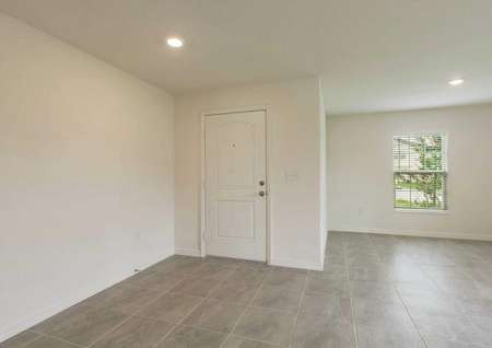 View of the front door from the Estero plan's living room that has tile flooring, white walls and recesses lighting.