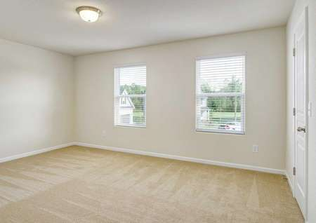Madison bedroom with two windows, light brown carpets, and white trim walls
