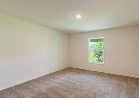 Spare room of the Anastasiafloor plan with a large window, light brown carpet and a light fixture on the ceiling.