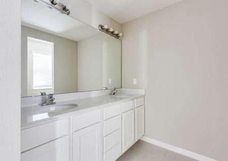 The master bathroom with dual sinks, quartz countertops and cabinets in the St. Johns floor plan.