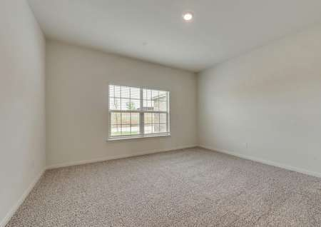 The master bedroom has brown carpet, white walls and a double-window with front yard views.