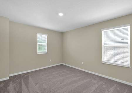 Sizable bedroom with multiple windows, allowing for plenty of natural light to enter.