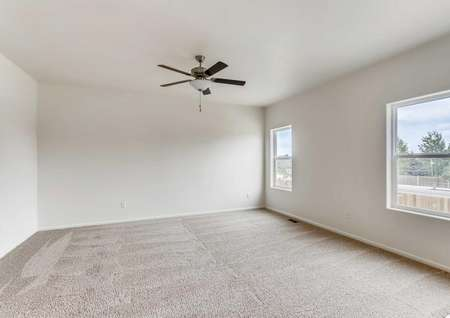 Columbia bedroom with two large windows, ceiling fan, and light color carpet