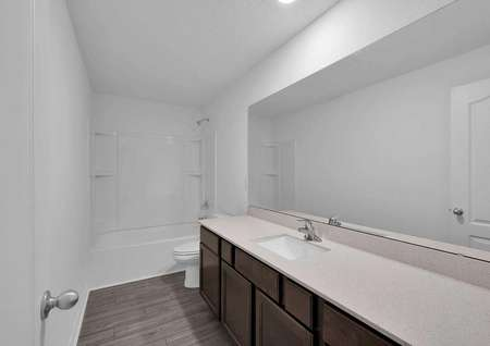 Long countertop space in one of the secondary bathrooms of the home.
