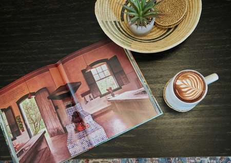 Coffee table with open book, coffee mug and decorations.
