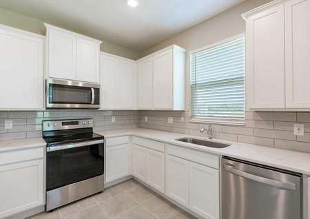 The kitchen with white wooden cabinets, quartz countertops and stainless steel appliances in the Tuscany floor plan.