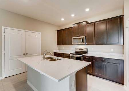 The kitchen in the Santa Maria model home. Quartz countertops, a large kitchen island, stainless steel appliances, large pantry and upgraded dark brown cabinets