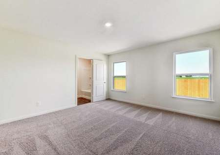 Medina master bedroom with two large side windows, soft brown carpeting, and private bathroom