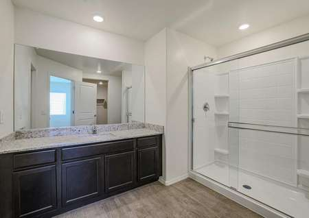 Master bathroom with granite countertops, espresso cabinets, and sparkling white shower with glass sliding doors.