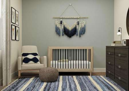 Rendering of a bedroom decorated as a nursery. The room has a light blue accent wall, window and is furnished with a crib, armchair, dresser and round mirror. The carpeted flooring is covered by a blue-and-white striped rug.