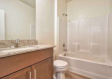 A secondary bathroom in the Sunflower floor plan with brown cabinet hardware, granite countertops and a tub/shower.