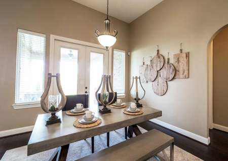 Dining room with light fixture, large table and hardwood floors.
