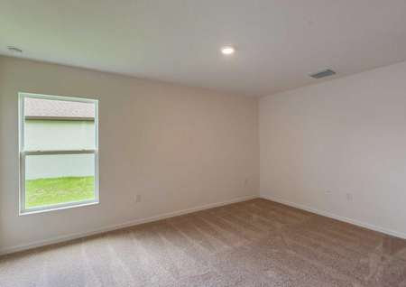 The Estero floor plan's spaciousmaster bedroom along with white walls, carpet, a window and an overhead light fixture.