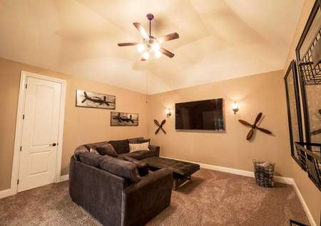Media room with sectional, tv and ceiling fan.