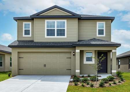 Large, two-story home with front yard landscaping, a covered front porch and a long driveway.