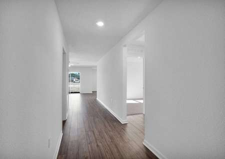 Entrance of new-construction home with a long hallway leading to an open-concept entertainment space.