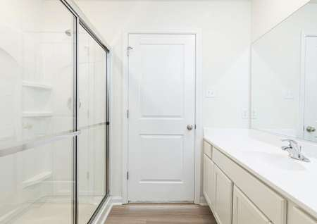 Master bathroom with long white vanity with one sink, one mirror, across from shower with sliding glass door.