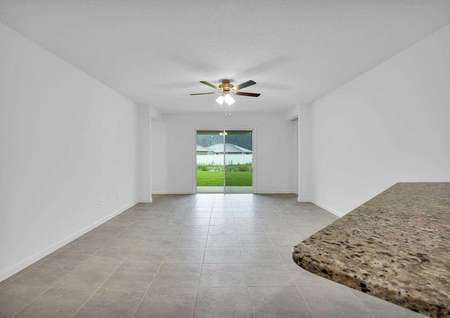 Sunnyside great room with ceramic tile floors, white on white walls, and overhead ceiling fan