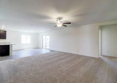 The spacious living room in the Guadalupe floor plan with carpet flooring, white walls and a ceiling fan with light.