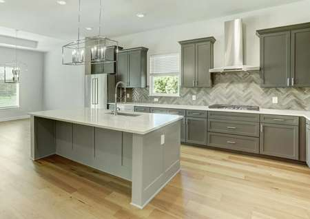 The kitchen has dark grey cabinetry, quartz countertops and stainless steel appliances.