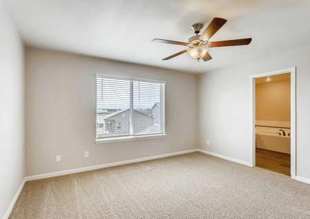 Roosevelt bedroom with private bathroom, brown ceiling fan with light fixture, and carpet