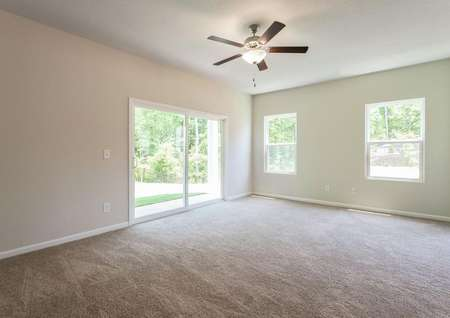 Spacious living room with ceiling fan and sliding doors to the back patio.