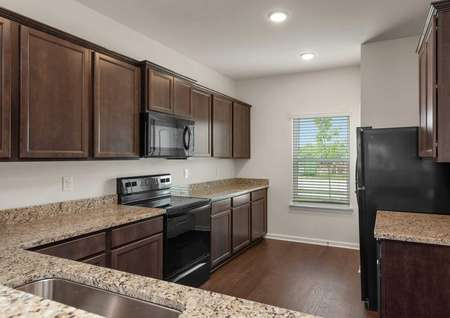 The Driftwood kitchen view showing dark brown crown molded cabinets with recessed lighting, black appliances, granite countertops with astainless steel sink, a window on the rear wall with 2