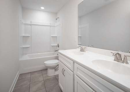 Fripp guest bathroom with two sinks, shower/tub unit, and modern white fixtures