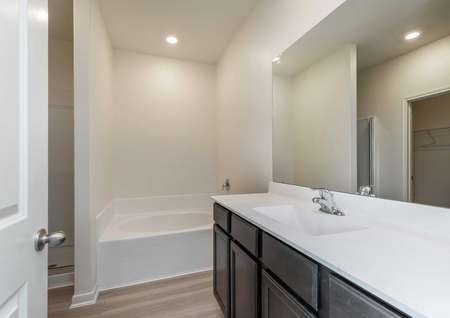 Maple bathroom with extended white vanity top, brown cabinets, and bath tub / shower unit