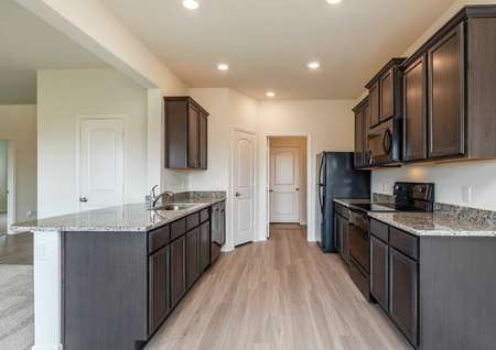 Cypress kitchen with recessed lights, brown custom cabinetry, and black appliances