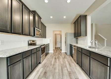 Oakmont floor plans kitchen with recessed lighting and dark brown cabinets.
