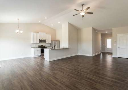Alexander great room with ceiling fan, chandelier, and white finish kitchen