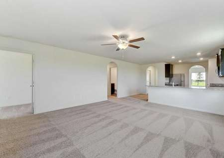 Frio great room with ceiling fan, carpeted flooring and view of kitchen and archways