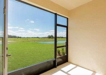 The back covered patio that has a mesh screen to keep out bugs and a view of a golf course that has a lake water hazard.