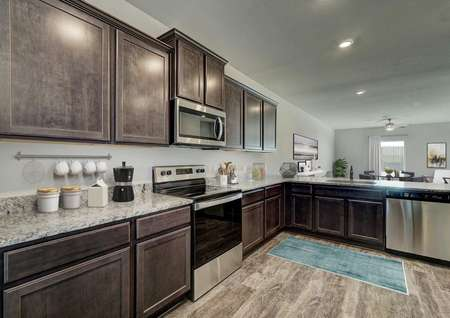 Staged kitchen with stainless steel appliances, brown cabinets and brown flooring.