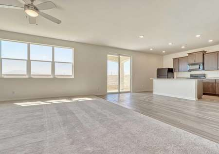 Aster great room with recessed lights in the kitchen, hardwood flooring, and white sliding patio door