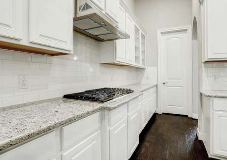 Bradley kitchen finished with dark wood floors, light color granite countertops, and white cabinetry