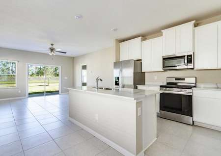 The kitchen in the Alafia floor plan that has an island with a sink, stainless steel appliancesand tile flooring.