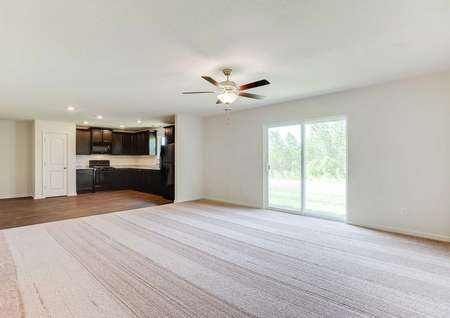 Aitkin great room with carpeting in the living room, overhead ceiling fan, and hardwood floors in the kitchen