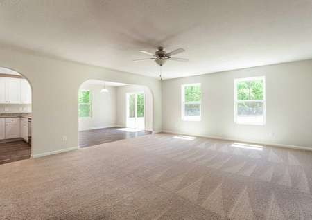 Fripp great room with dining nook, tan carpet, and windows