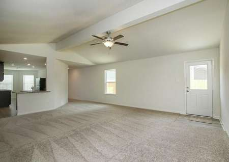 Pecos great room with carpeted floors, white back door with window, and access to kitchen