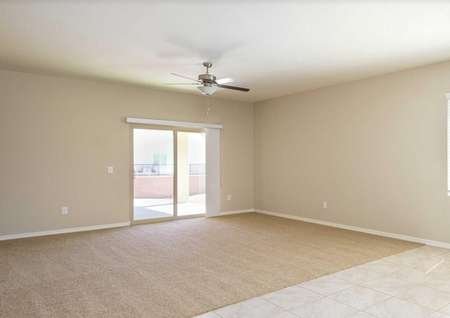 Prescott living room with tan carpet and sliding doors leading out to the covered patio.